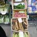 Az alsó két ládában főzőbanán van. Az alsó zöld 1,99 euró/kg, a sárga 2,20. Fölötte thai fokhagyma (10 dkg-1 euró). A zöld, hosszúkás cucc a keserű dinnye