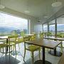 A lejtős oldalra felhúzott, parkosított belső udvarral és rámpával rendelkező éttermet a bázeli székhelyű Büning-Pfaue Kartmann Architekten tervezte.