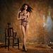 A modell,Caitlin erős púder színű szettben, masnikkal, háttérben szellemmel az Agent Provocateur új kampányában.