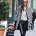 Miranda Kerr feketével szegett szürke kabátban sétáltatja gyerekét