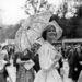 1959. június 7: Daniele Saintoin modell tüllernyővel és elegáns ruhában néz lóversenyt a Chantilly versenypályán.