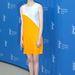 Emma Stone egy nude Louboutin cipő és narancs ajkak mellett döntött.