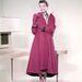 Katherine Hepburn hosszú rózsaszín kabátban 1955-ben.