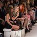 Egy jellemző kép a divathétről: az első sorban hírességek és divatszerkesztők ülnek, lábuknál értékes ajándékokkal teli ajándékszatyrok pihennek.