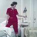 Kétrészes, tengerész egyenruha inspirálta piros pizsamában készülődik lefekvéshez a modell. Ilyet ma már nem látni.