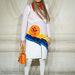 Fehér bőrnadrágot, cipőt vett fel hozzá és egy narancssárga táskát cipelt magával.