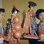 Egy 1954-es hawaii fesztiválon hagyományos japán viseletbe öltözött hölgyek tartanak kimonót viselő babákat