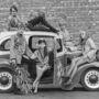 Hippimobil 1968-ban: modellek pózolnak egy kocsival, a kor hippidivatjának megfelelően öltözve. A kocsi fontos eleme a hippi-kultúrának.